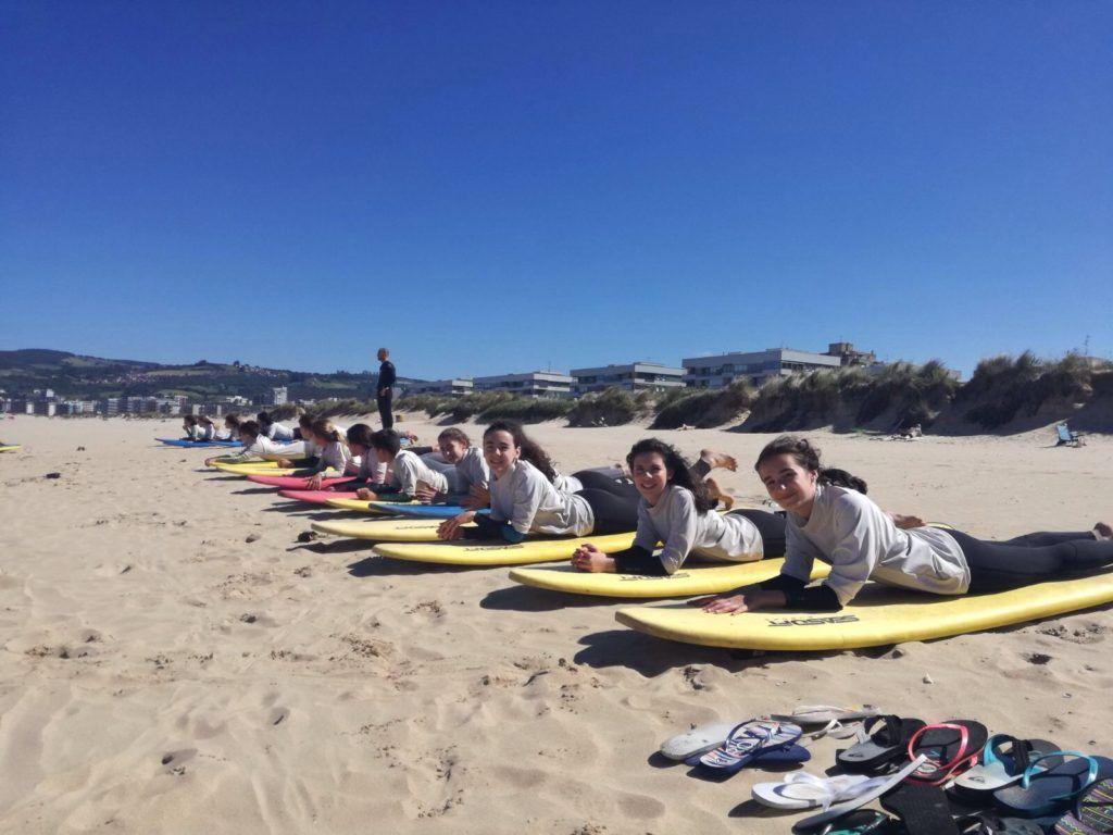 Grupo en la playa cuando comienzan a recibir las primeras instrucciones para realizar surf
